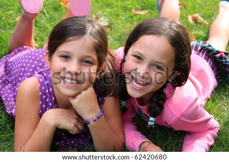 Two young girls in the ages of ten and eight that could be sisters or best friends laying on the grass and smiling whitle wearing colorful clothing - stock photo