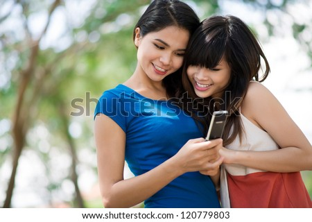 Two young girls massaging on cell phone - stock photo