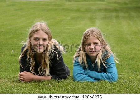 Two young girls on a grassy hill - stock photo