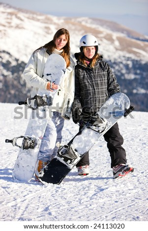 Two young girls on snowboard - stock photo