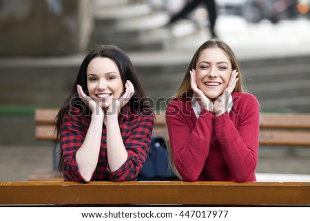 Two young girls posing outdoors - stock photo