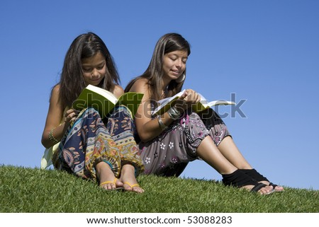 Two young girls reading books on the park - stock photo