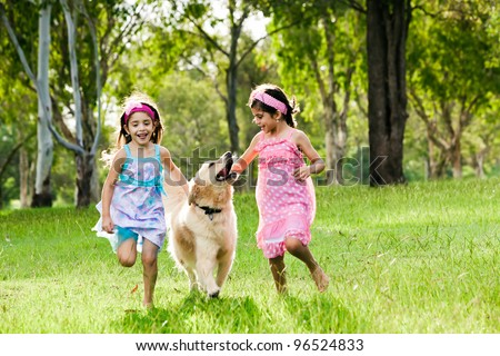 Two young girls running with golden retriever in park - stock photo