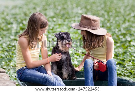 Two young girls sitting on boat with their dog, green background with sun rays - stock photo