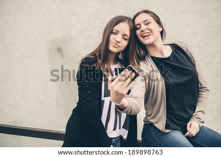 Two young girls smiling using smart phone - stock photo