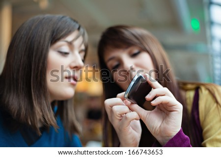 Two young girls smiling using smart phone in a cafe. - stock photo