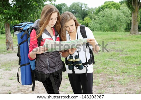 Two young girls with backpacks view map - stock photo