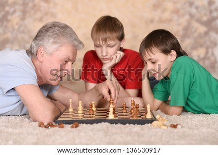 two young guys and their grandfather playing chess at home - stock photo