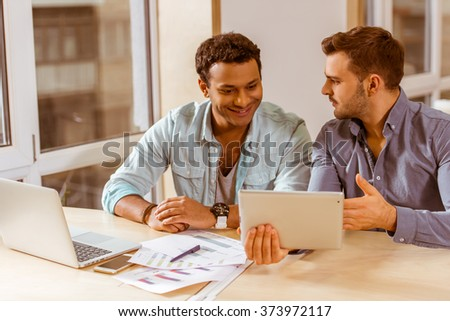Two young handsome businessmen in casual clothes smiling, talking, discussing ideas, using laptop and tablet while working in office - stock photo