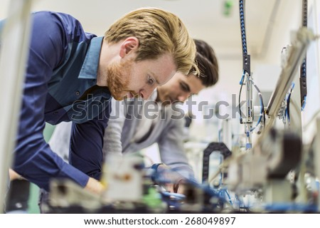 Two young handsome engineers working on electronics components and fixing broken chips - stock photo
