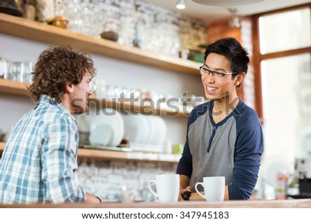 Two young handsome men drinking tea and talking in cafe  - stock photo