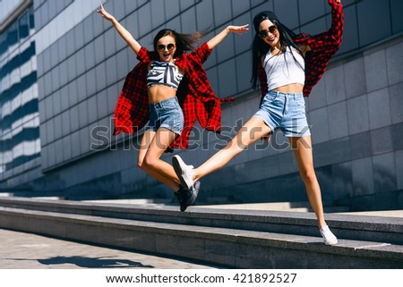 Two young happy hipster girls in sunglasses having fun, smiling, laughing, jumping, walking outdoor on the street, summer relax concept - stock photo