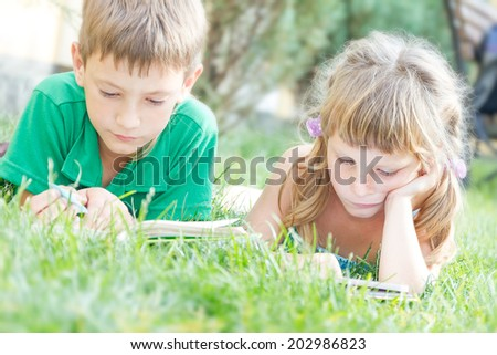 two young happy kids, children reading books on natural background, outdoors - stock photo