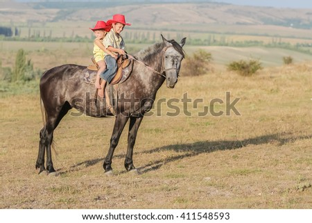 two young happy kids riding a horse on farm, outdoor portrait on rural background - stock photo