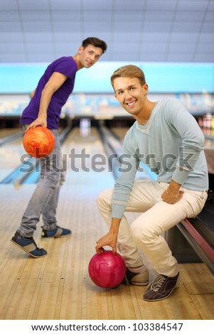 Two young happy men play in bowling club; right man sits; left man throws ball and looks at camera; focus on right man; shallow depth of field - stock photo