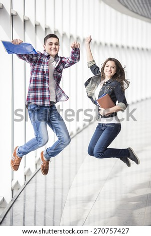 Two young happy students jumping in college. - stock photo
