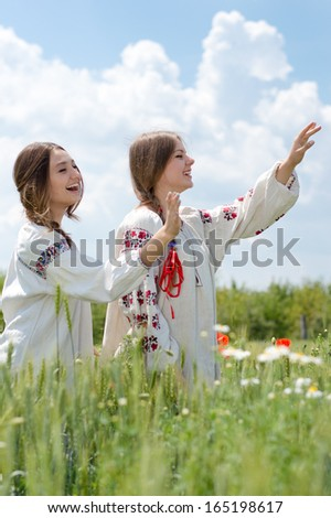 Two young happy women girl friends in traditional Ukrainian dress in wheat field on summer outdoors background - stock photo