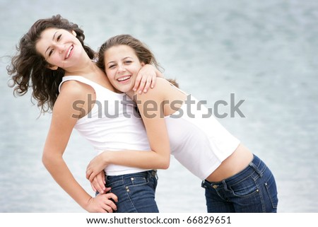two young happy women on sea background - stock photo