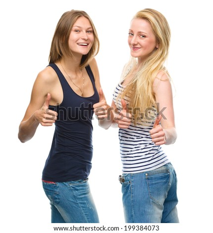 Two young happy women showing thumb up sign using both hands, isolated over white - stock photo
