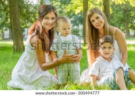 two young happy women with kids on natural green background, smiling happy girls with kids outdoor portrait - stock photo