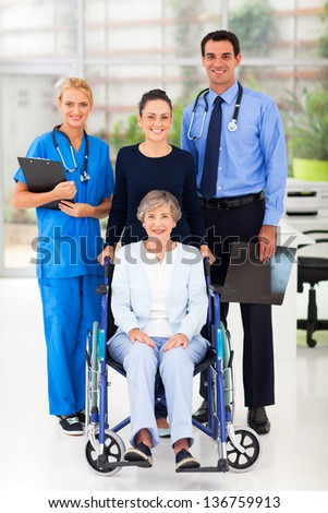 two young health workers and senior patient - stock photo