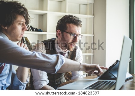 two young hipster stylish elegant men working with notebook and tablet at home  - stock photo