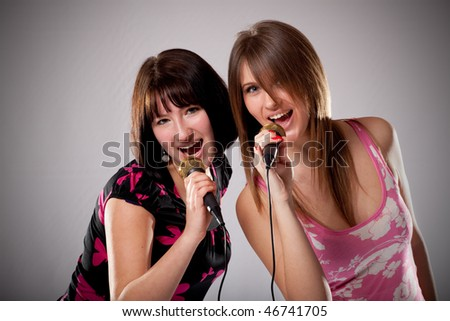 two young karaoke girls - stock photo