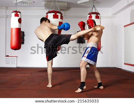 Two young kickbox fighters training in the gym - stock photo