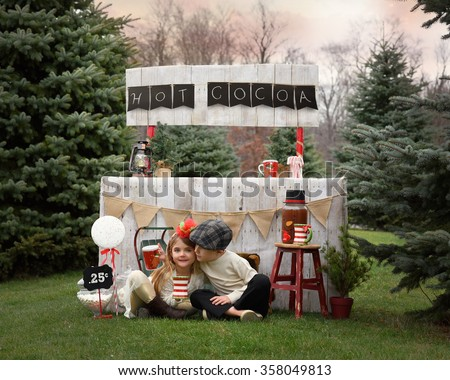 Two young kids are selling hot cocoa outside with a wooden stand for an entrepreneur or business concept. - stock photo