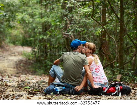 Two young kissing people sitting on the backpack in the forest - stock photo