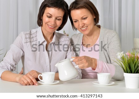 Two young ladies are having tea time - stock photo