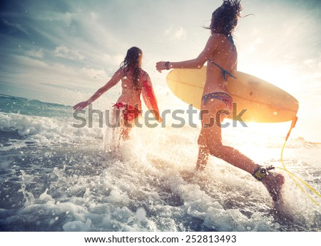 Two young ladies surfers running into the sea with surf boards - stock photo