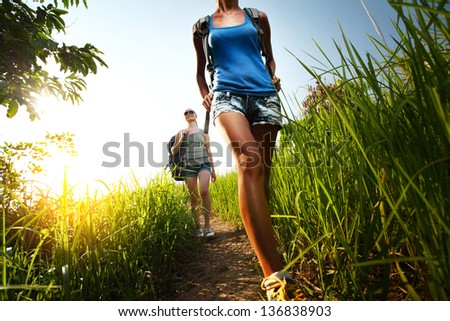Two young ladies walking with backpacks on a thin path through a lush tropical meadow - stock photo