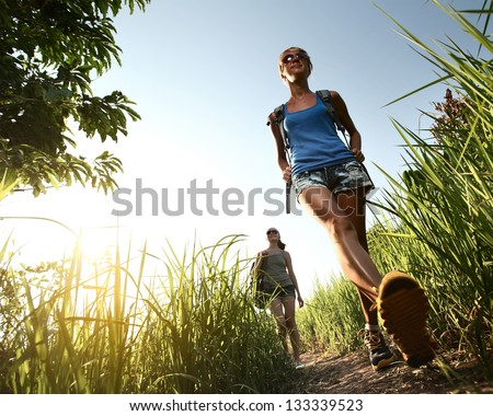 Two young ladies with backpacks walking through green tropical meadow - stock photo
