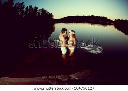 Two young lovers in a lake at night. Girl and man at sunset in the lake. - stock photo