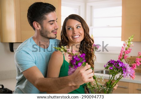 Two young lovers laugh and play in happiness lovingly putting flowers from their garden into a vase - stock photo