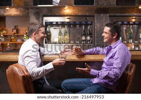 two young man talking at counter. two friends sitting in bar and drinking whisky - stock photo