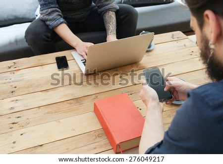 two young man using laptop and a smartphone.focus on the phone - stock photo