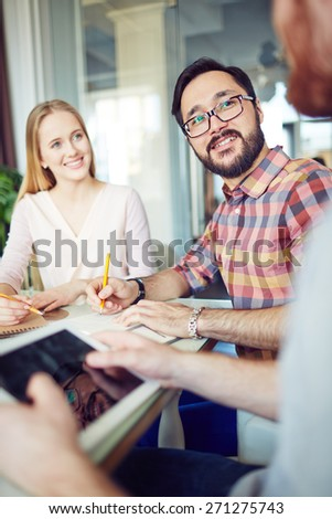 Two young managers writing down ideas of their colleague - stock photo