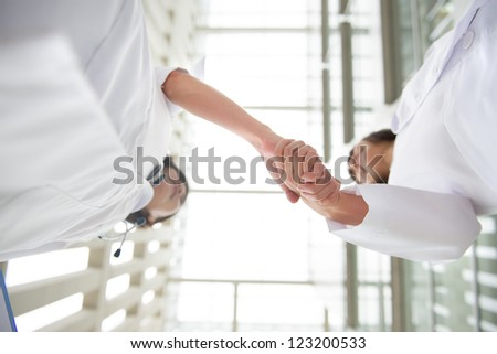 Two young medical doctors shaking hands, teamwork - stock photo