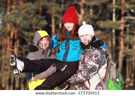 two young men and women group of people, friends and couples enjoy winter activities in winter forest, enjoy life and hugging - stock photo