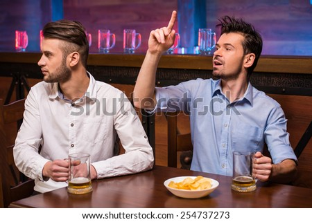 Two young men are sitting in pub and making order. - stock photo