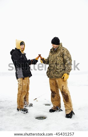 Two young men clink beers bottles while ice fishing. Vertical shot. - stock photo