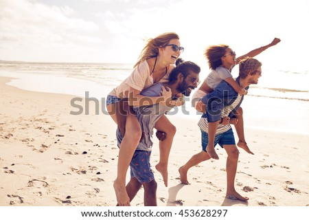 Two young men giving their girlfriends piggyback rides at the beach. Cheerful young friends enjoying summertime on the beach. - stock photo