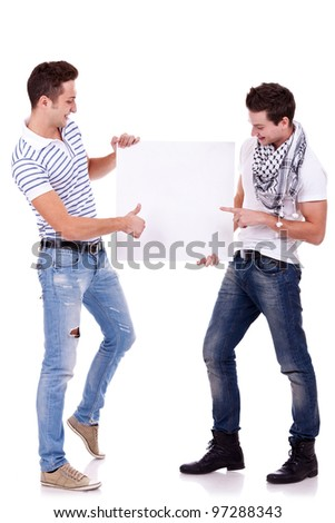 two young men holding a blank board on white background, one pointing to it and one gesturing ok with thumbs up - stock photo