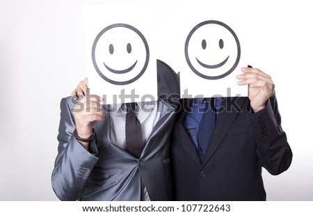 Two young men holding smiley faces. - stock photo