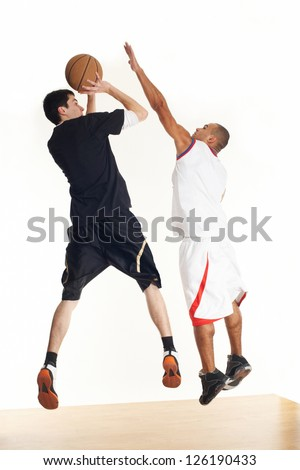Two young men in basketball uniform playing basketball on white background. - stock photo