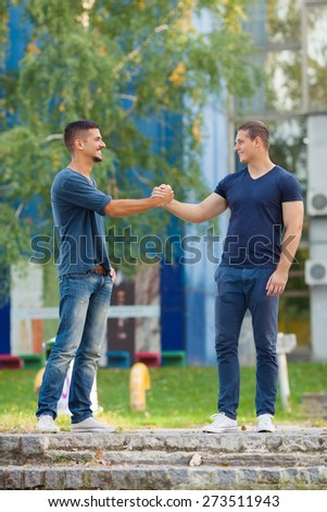 Two young men meeting in front of the college building - stock photo