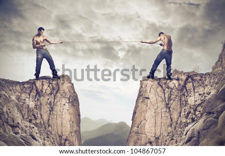 Two young men playing tug of war over a precipice - stock photo