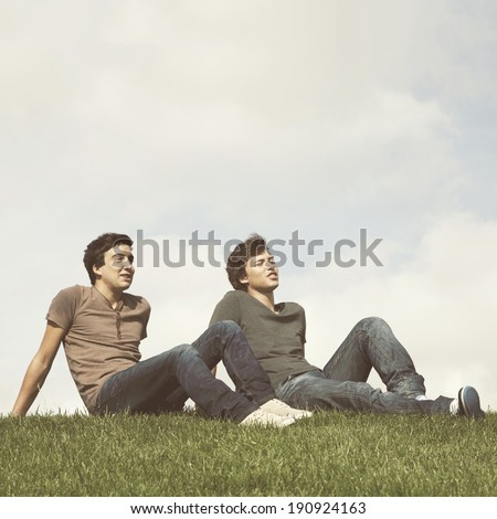 Two young men sited on the grass looking away - stock photo